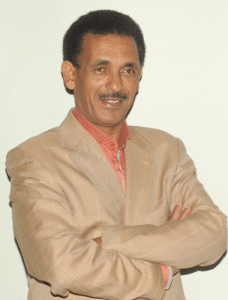 Image of Dr. Berhan Ahmed in a brown suit looking to the right of the camera with a beige background