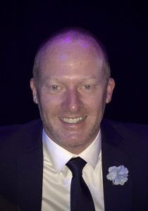 Image of David Carney in a blue suit with the flower and a dark blue background