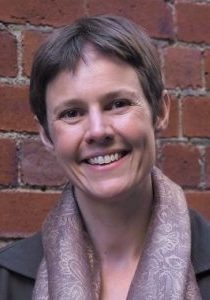 Image of Dr Jennifer Jackson smiling at the camera with a brick wall in the background
