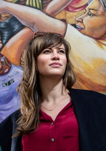 Image of Sara El-Amine in a red top with a mural in the background